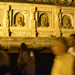 Pilgrims walking past the ornately caved walls of the Mahabodhi Temple // © 2013 Deborah Dimond