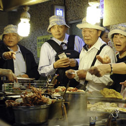 Visitors order the oyster omelet and the Taiwanese sausage at Taipei's famous Shilin Night Market. // © 2014 Mindy Poder