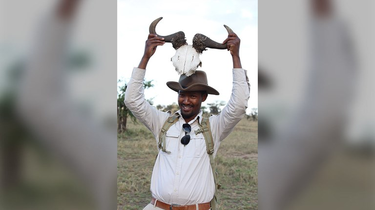 Four Seasons guide Isack holds up a hartebeest carcass and explains its uses.