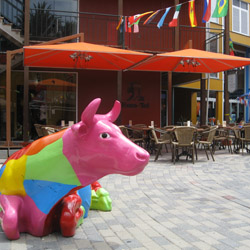 <p>The center plaza in Rif Fort offers a family-owned cheese shop and this decorative cow, which doubles as a bench. // © 2014 Jessica...