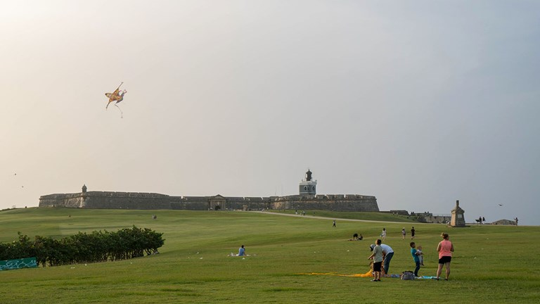 Local families flying kites in front of El Morro