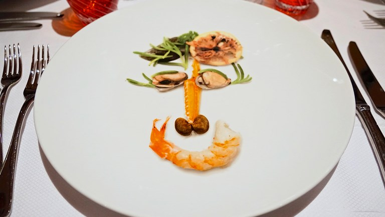 "Rudi's Sel de Mer specialty restaurant showcases Rudi Sodamin's playful ""food faces"" charger plates."