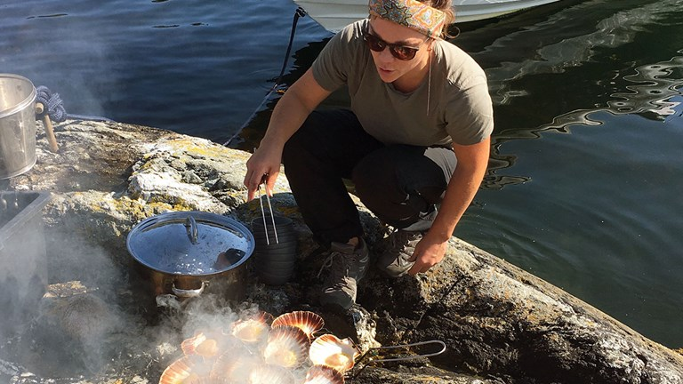 A guide demonstrates cooking seafood in the wild.