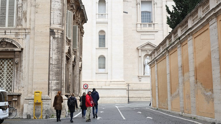 A guide walks Access Italy guests through the Vatican's empty streets while tourists wait in line nearby.
