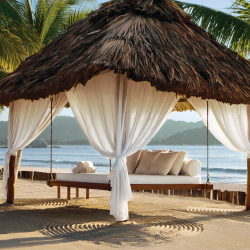 Thatched palapas for guests line the beach // © 2014 Viceroy Hotels and Resorts