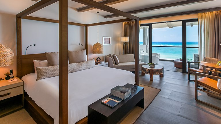 An Alcoba Ocean Front guestroom features a balcony with a hydro spa tub and a lounging area.