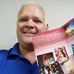 <p>Hugh Sheppard, owner of Encore Travel, Luxury Travel Concierge, holding a sample of a card created by SendOutCards. // © 2014 Hugh...