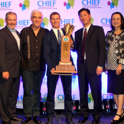 Adam Stewart, CEO of Sandals Resorts International (center), celebrates his 2015 Caribbean Hotelier of the Year award win. // © 2015 Sandals Resorts...