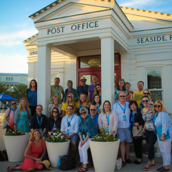 "Attendees of the fourth annual TMS Family Travel Summit pose outside ""the most photographed post office in America"" in Seaside, Fla. // © 2016 Visit..."