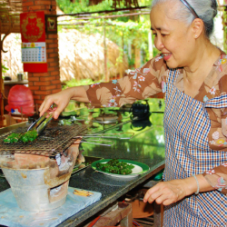 <p>Guests learn from legendary chef Nguyen Dzoan Cam Van in her outdoor kitchen. // © 2016 Access Trips</p><p>Feature image (above): Access Trips'...
