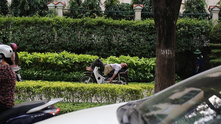 A man rests on his bike in the afternoon in HCMC, a metropolis of 12 million people.
