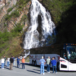 <p>A tour group stops at a waterfall during a land tour. // © 2015 John Hall's Alaska</p><p>Feature image (above): Guests are introduced to an Alaska...
