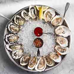 <p>Hungry? Order a round of oysters and then some at Mignonette. // © 2015 Mignonette</p><p>Feature image (above): Surfcomber Hotel in South Beach is...