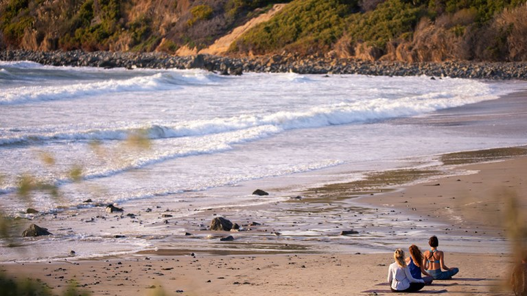 Top California resorts offer wellness activities, such as yoga and guided walks, on the beach.