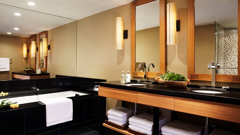 The large bathroom in a one-bedroom suite offers a soaking tub and his-and-hers vanity sinks.