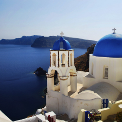 This blue-domed church is one of the landmarks of the town of Oia. On which island is it?// © 2014 Thinkstock/ extravagantni