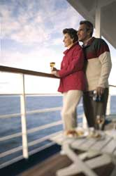 Couple looking at sea from balcony on Regent Seven Seas ship // © Regent Seven Seas