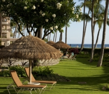 Oceanfront lawn chairs under thatched umbrella, Kaanapali Alii, Maui. // © 2011 Classic Resorts