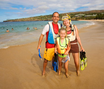 A family with Trilogy Excursions poses at Hulopoe Bay, in front of Four Seasons Resort Lanai at Manele Bay. // © 2012 Trilogy Excursions