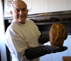 Pratt Morales, owner of the Golden Crown Panderia, with a loaf of green chile bread. // © Fran Golden 2010