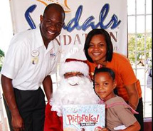 <p>O'Brian Heron (left) of Beaches Sandy Bay and Jervene Simpson, of Sandals Resorts Negril pose with Santa Claus and a Mount Airy All Age student...