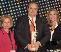Angela Gonzales-Rowe, of LHA (left) and Nancy Poor, of Wyndham Worldwide (right) present Carlos Rodriguez with the 2011 Estrella Award for Latino...
