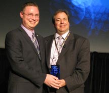 Coleman (left) accepts the award from ASTA president and chairman, Chris Russo.