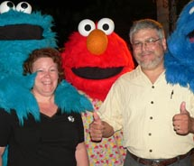 Travel agents Denise and Paul Hangsleben of Travel Your Way network with Cookie Monster, Elmo and Grover at Sandals Royal Caribbean, Sandals Cay. // ©...