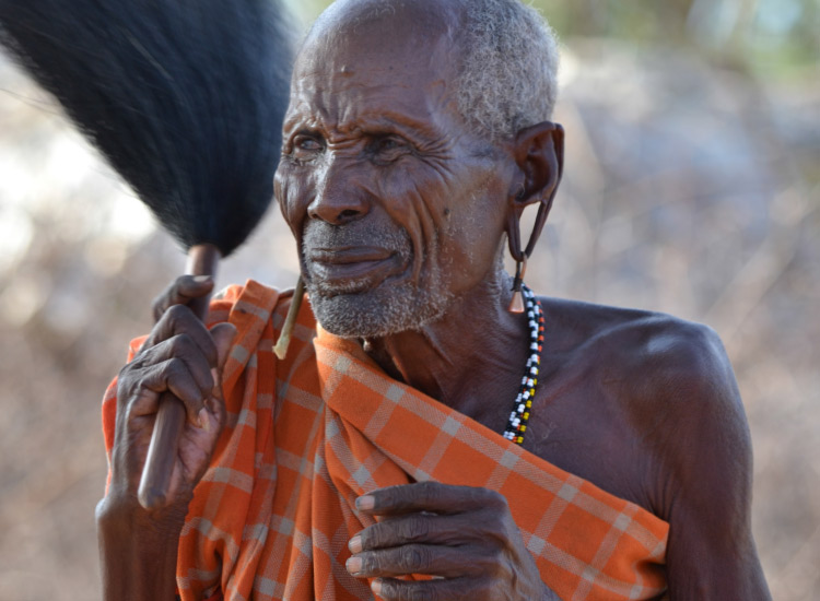 On an Abercrombie & Kent safari in Africa, a Samburu elder welcomes the tour group to his village. // © 2015 Mindy Poder
