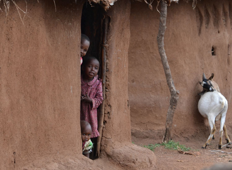 Maasai children peek out from their home. // © 2015 Mindy Poder