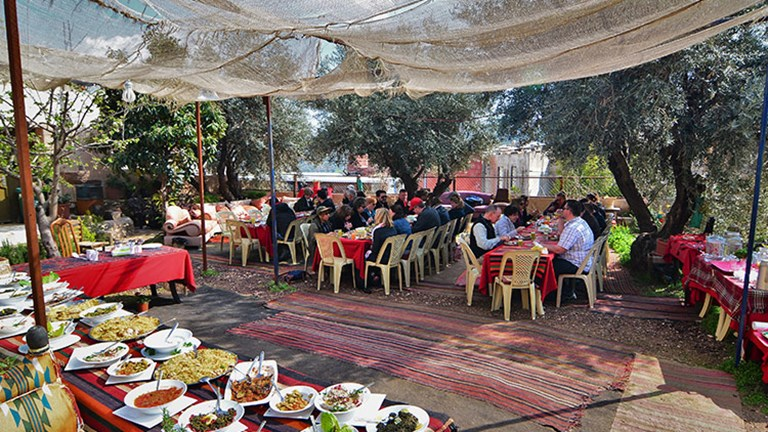 Visitors enjoy lunch under the trees at Bait Khayrat Souf. // © 2018 Tourism Cares