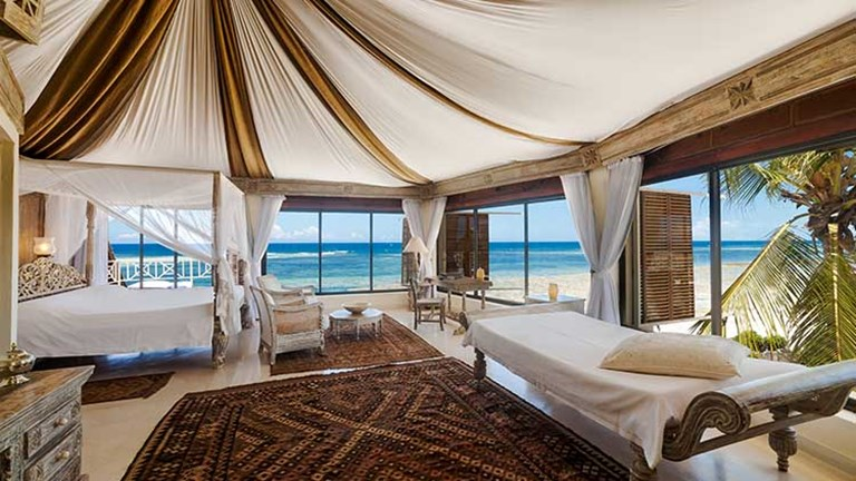 The master bedroom on the top floor of the Cliff Villa includes handcrafted furniture and stunning panoramic views. // © 2016 Alfajiri Villas