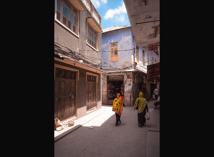 Women walk through Stone Town's narrow streets. // (c) 2013 Bob Demyan