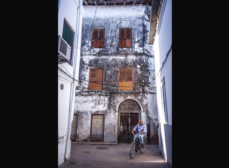 A Zanzibari man rides his bicycle through Stone Town. // (c) 2013 Bob Demyan
