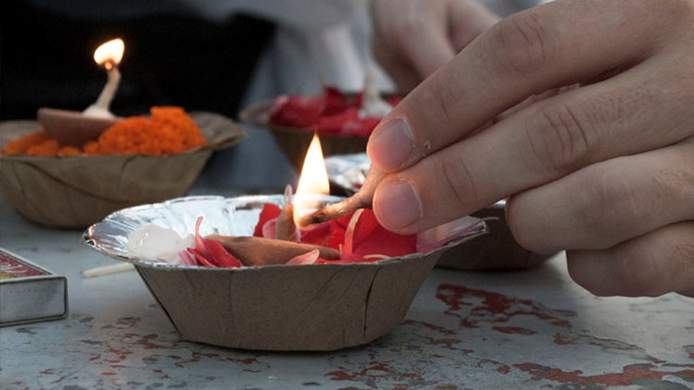 As the sun rises, it is customary to make a wish while releasing a diya into the water. // © 2014 Mindy Poder