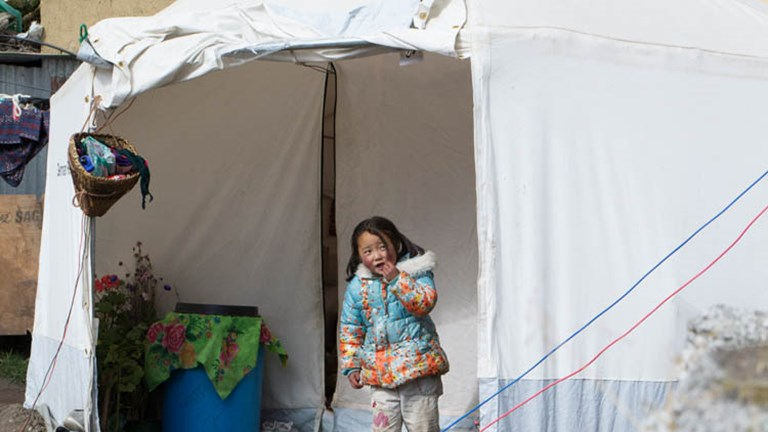 A young girl peeks out of a tent donated by an international aid group. // © 2015 Mindy Poder