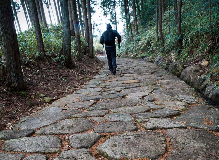 A member of the Walk Japan Nakasendo Way tour walks up a stone path toward the historic postal town of Shinchaya.  // © 2014 Mark Edward Harris