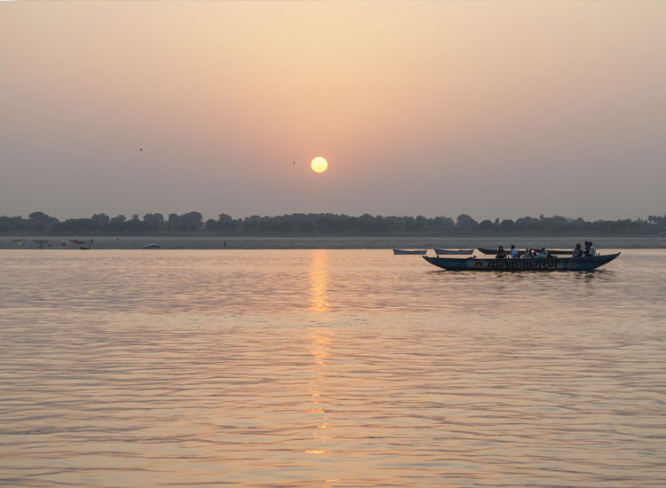 Experiencing Varanasi's sunrise by boat on the Ganges River has become popular among tourists. // © 2014 Mindy Poder
