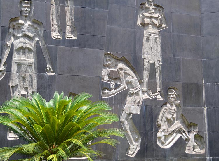 At Hoa Lo Prison Museum, a courtyard wall is carved with figures illustrating the prison's dark history. // © 2016 Marilyn Jones