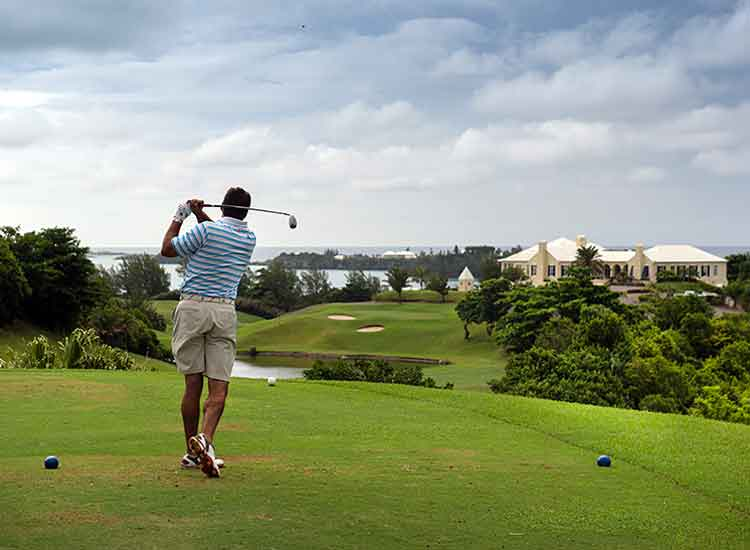A golfer takes a swing at the 18th hole at Tucker's Point Club, one of Bermuda's best golf courses.  // © 2013 Mark Edward Harris
