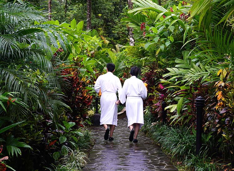 A couple wanders through Tabacon Hot Springs' lush gardens, wearing bathrobes provided for guest use. // © 2017 Janice Mucalov