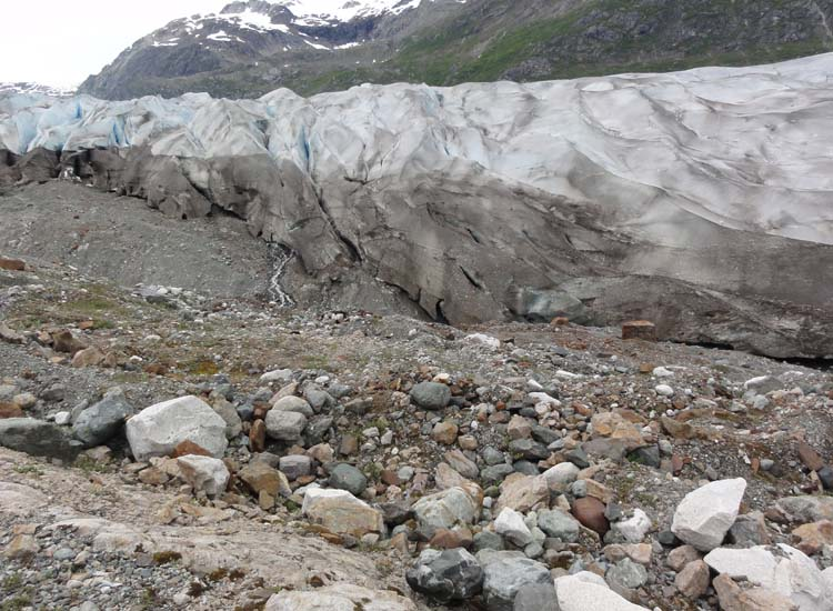 Rubble and silt resulting from the glacier's slow recession are visible at the edges of the ice sheet. // © 2014 Dennis Sides