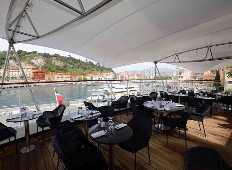 Lunch venue Veranda offers expanded outdoor seating, along with a courtyard and garden wall. At night, it transforms into dinner spot Candles. // © 2016 Windstar Cruises