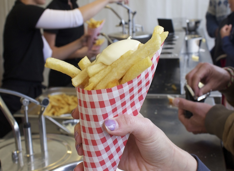 Another snack often eaten on the go are frites, served in a paper cone and topped with mayonnaise. // © 2014 David Wade