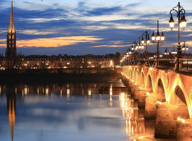 Take a romantic walk over an illuminated bridge in Bordeaux. // © 2015 iStock