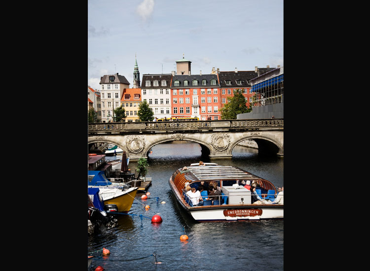 A boat tour is another great way to explore Copenhagen, which is crisscrossed with many canals and elegant bridges, such as the one that stretches over Frederiksholm Canal. // © 2014 Ty Stange