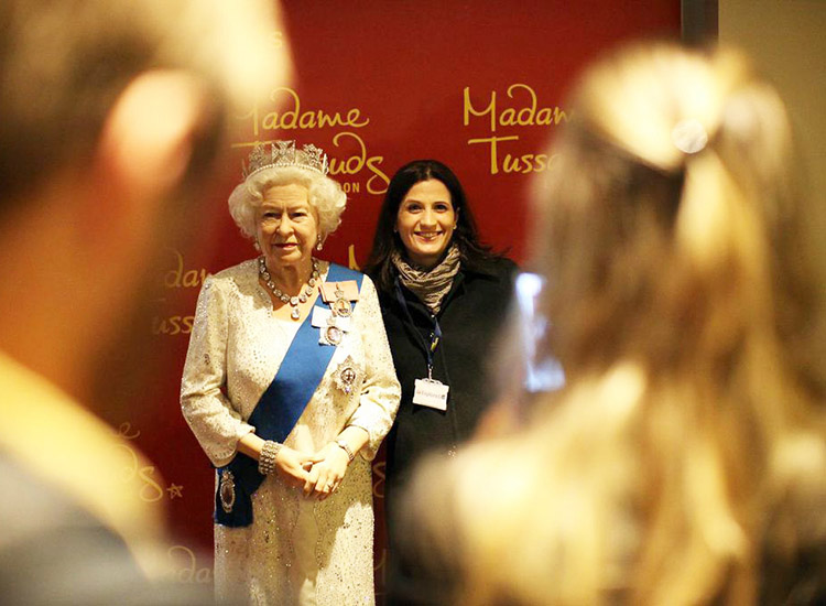 A guest of ExploreGB, VisitBritain's new flagship event, poses with a wax representation of Queen Elizabeth II. // © 2015 VisitBritain