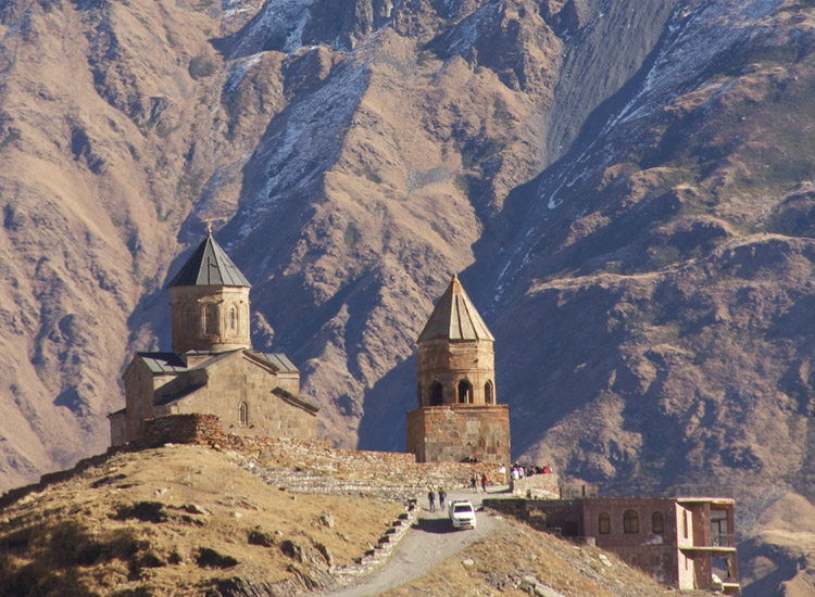 Mount Kazbegi looms over the 14th-century Gergeti Trinity Church in Georgia. // © 2014 Devin Galaudet