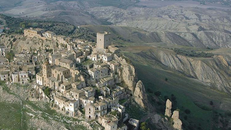 An aerial view of Craco, Italy, shows its unique surrounding landscape. // © 2017 Creative Commons user basilicatatravel