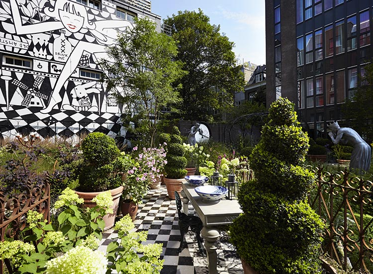 An Alice in Amsterdam mural is on display in the hotel's private garden. // © 2016 Andaz Amsterdam, Prinsengracht